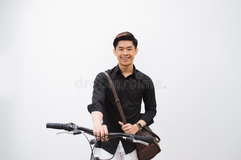 Junger h?bscher asiatischer Mann gegen den Hintergrund der wei?en Wand sitzt auf einem Fahrrad lizenzfreie stockfotos