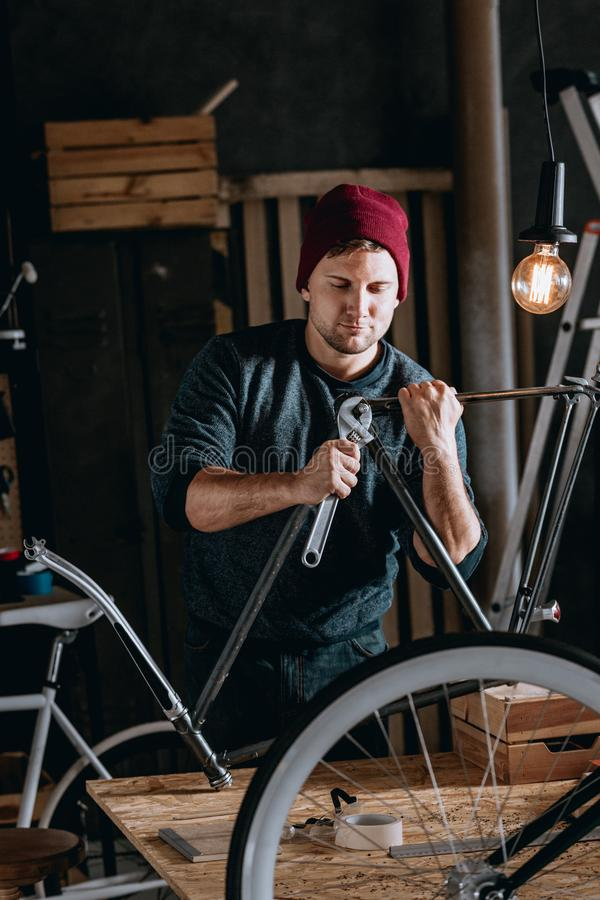 Junger Heimwerker, der Fahrrad repariert lizenzfreie stockfotos