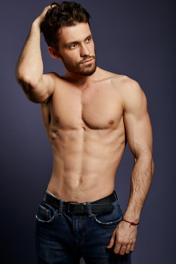 Junger hemdloser sexy Kerl, der seine Hand auf Kopf hält und beiseite schaut stockbilder