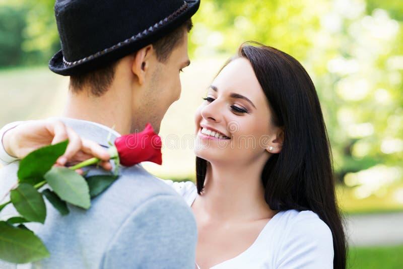 Junger Herr, der eine Rose seiner Liebe im Park darstellt lizenzfreie stockbilder