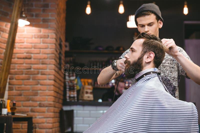 Junger Herrenfriseur, der einem bärtigen Mann den Haarschnitt der Männer macht stockfotografie