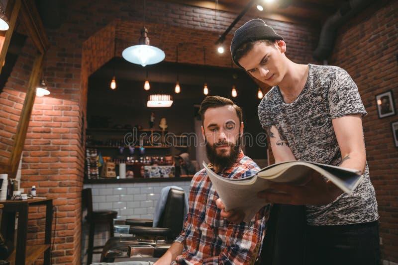 Junger Herrenfriseur und bärtiger Kunde, die durch Zeitschrift schaut lizenzfreie stockfotografie