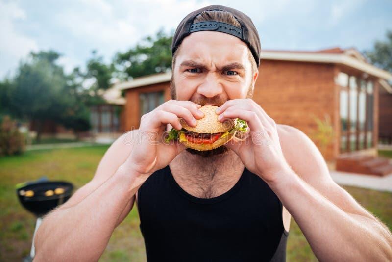 Junger Hippie-Kerl, der draußen köstlichen Burger isst lizenzfreies stockfoto