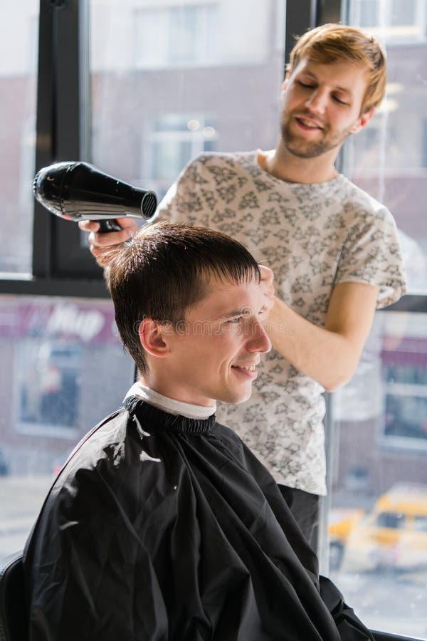 Junger Hippie-Kerl im Friseursalon, Friseur, der Haar mit den Scheren, blow-drying schneidet Konzeptmannplatz stockfotos