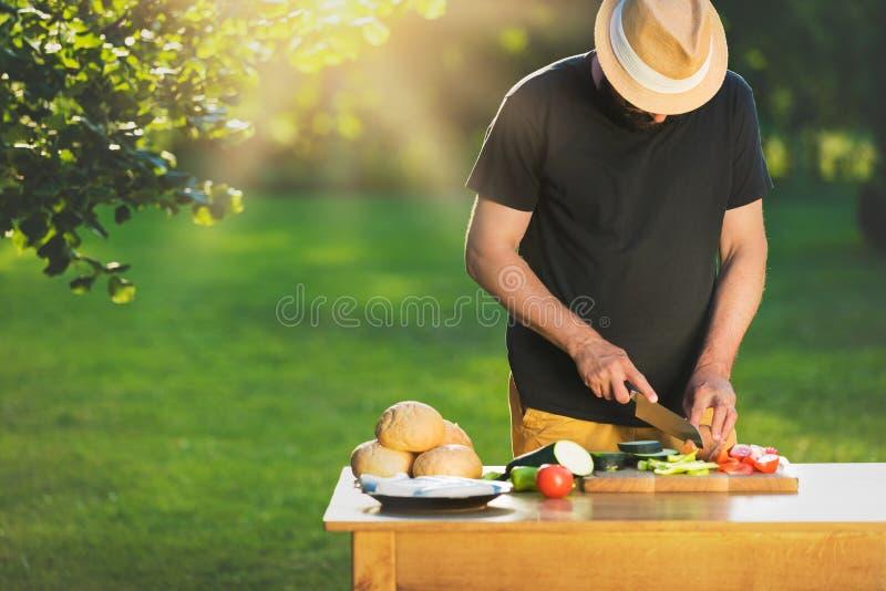Junger Hippie-Mann, der Lebensmittel für Gartengrillpartei, Sommergrill zubereitet stockfotos
