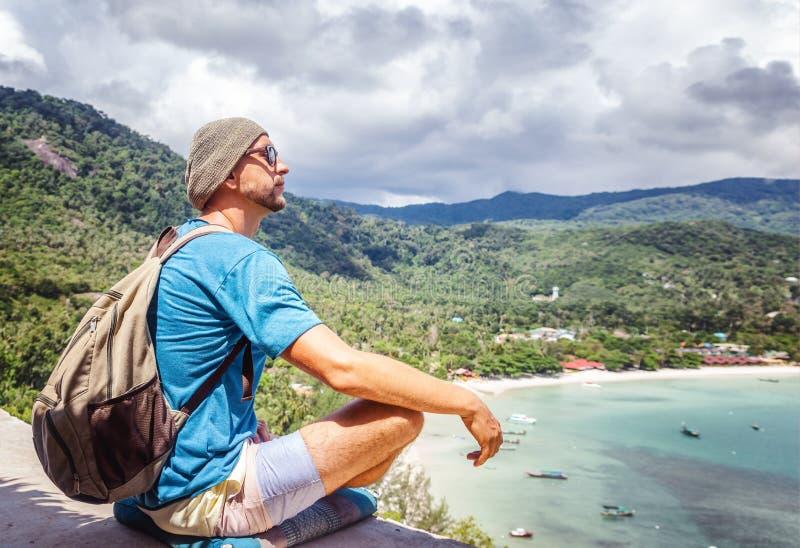 Junger Hippie-Mann, der am Seestandpunkt mit Rucksack sitzt Trave lizenzfreie stockfotos