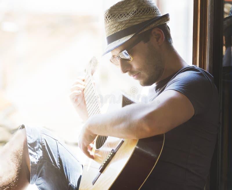 Junger Hippie-Mann spielt die Gitarre stockbild