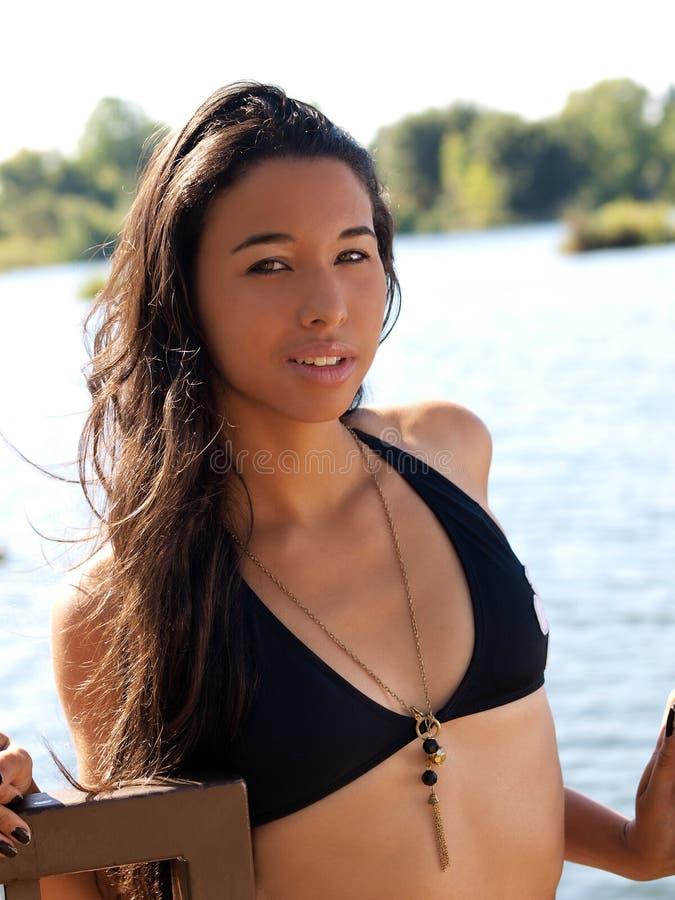 Junger hispanischer Frauenschwarz-Bikinioberseitenfluß stockfotografie