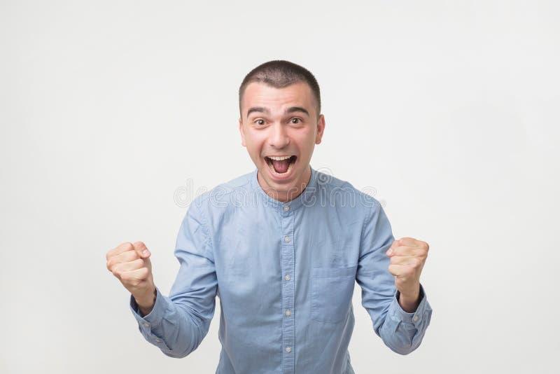Junger hispanischer Mann im blauen Hemd Sieg seines Teams über grauem Hintergrund feiernd stockbild