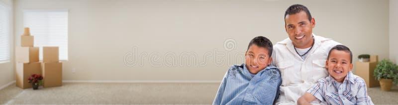 Junger hispanischer Vater und Sohn-Familie innerhalb des Raumes mit Kasten-Verbot lizenzfreie stockfotos