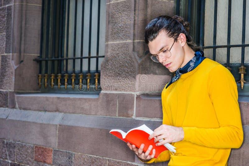 Junger Hispanoamerikaner-Mann, der rotes Buch draußen in New York liest stockfoto