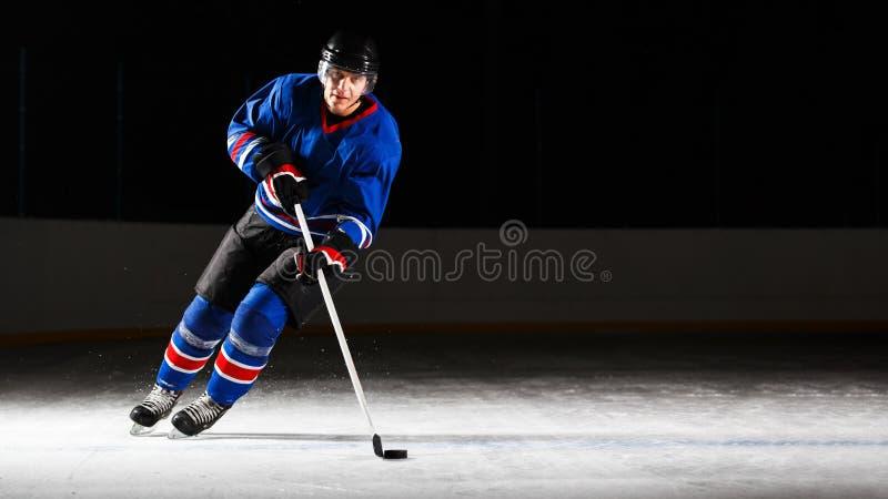 Junger Hockeyspieler, der auf Eisbahn im Angriff eisläuft stockfotografie