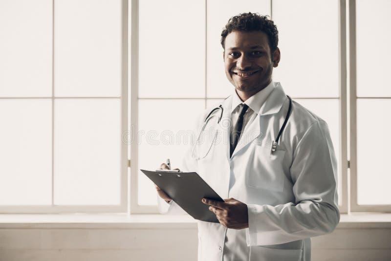Junger indischer Doktor in den weißen einheitlichen Schreibens-Anmerkungen stockfotografie