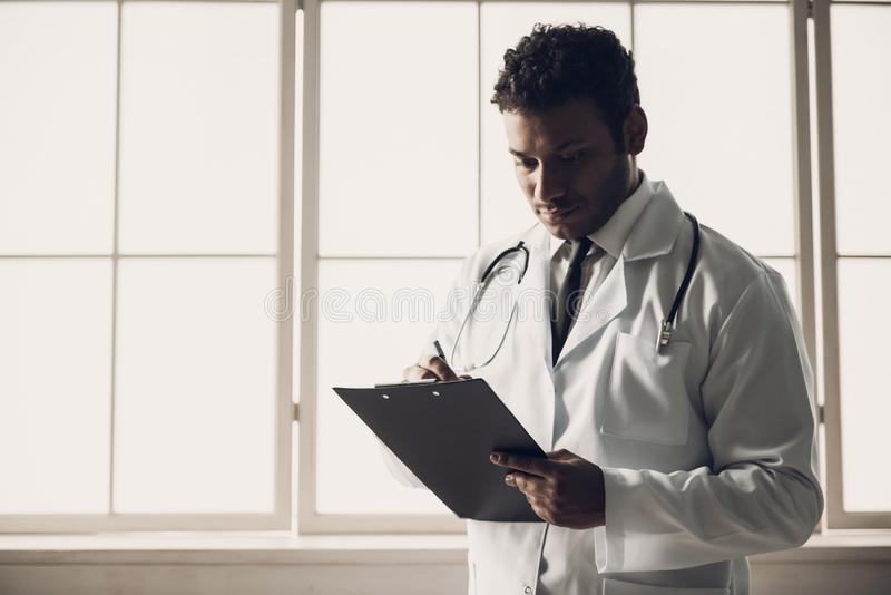 Junger indischer Doktor in den weißen einheitlichen Schreibens-Anmerkungen lizenzfreie stockbilder