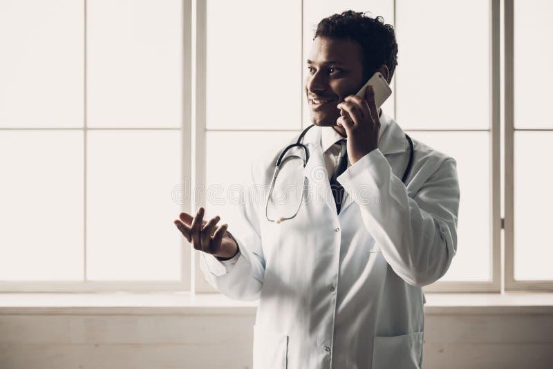 Junger indischer Doktor in der weißen Uniform mit Telefon stockbild