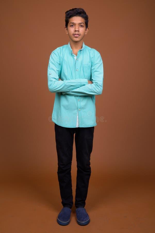 Junger indischer Junge, der das blaue Hemd schaut intelligent gegen Braun trägt lizenzfreies stockfoto