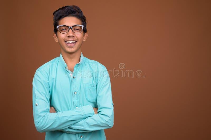 Junger indischer Junge, der das blaue Hemd schaut intelligent gegen Braun trägt stockfotografie