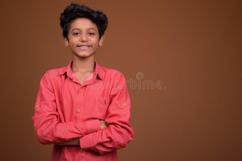 Junger indischer Junge, der intelligente Freizeitbekleidung gegen braunes BAC trägt stockbilder