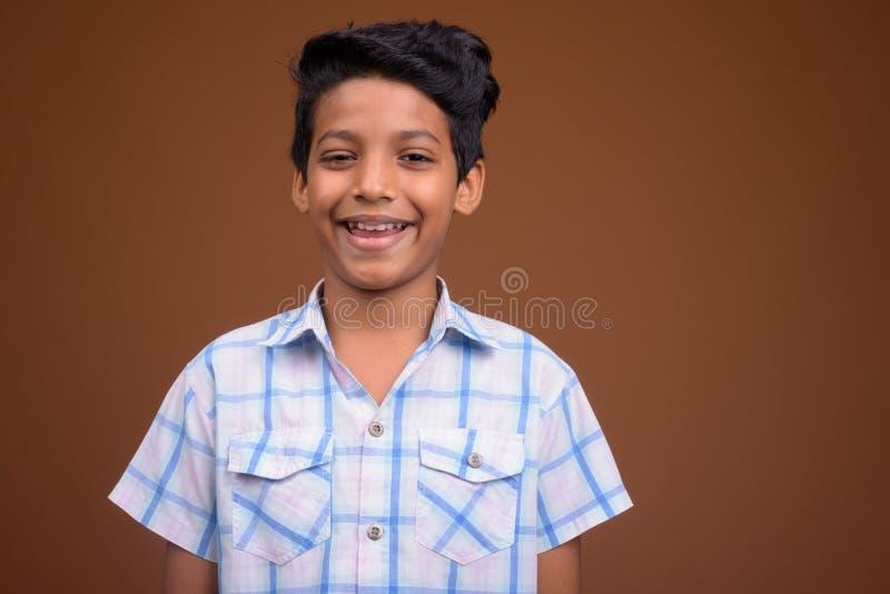 Junger indischer Junge, der kariertes Hemd gegen braunes backgroun trägt stockbild