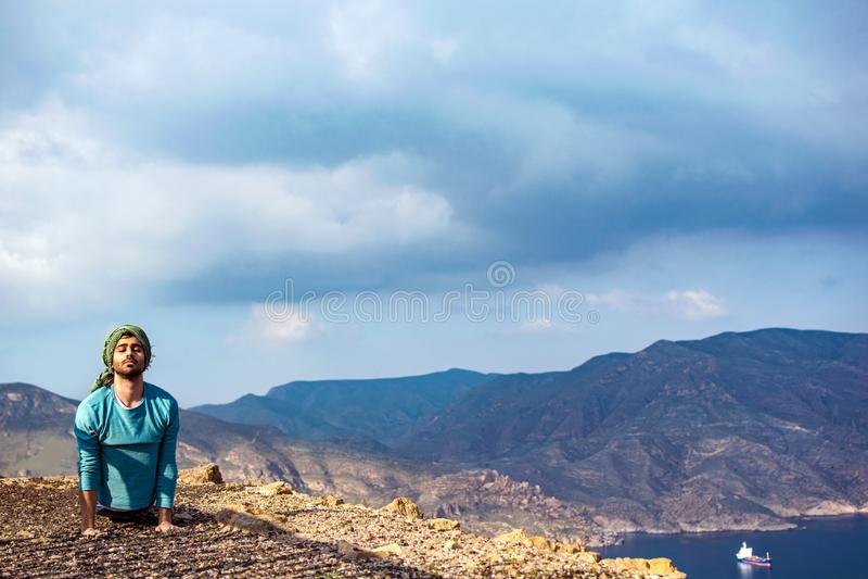 Junger indischer Mann auf dem Bergkupperand-Klippenfelsen, der Yoga durchführt lizenzfreie stockbilder
