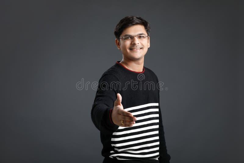Junger indischer Mann, der vorbei ein Abkommen macht stockbild