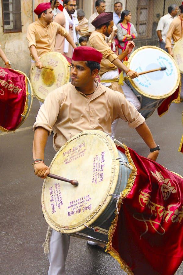 Junger indischer Mann, gekleidet dhol-taasha während Ganapti Visarjan traditionsgemäß, spielend stockbilder