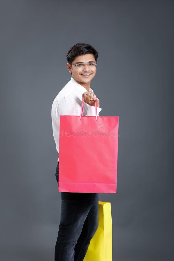 Junger indischer Mann mit Einkaufstaschen lizenzfreies stockfoto