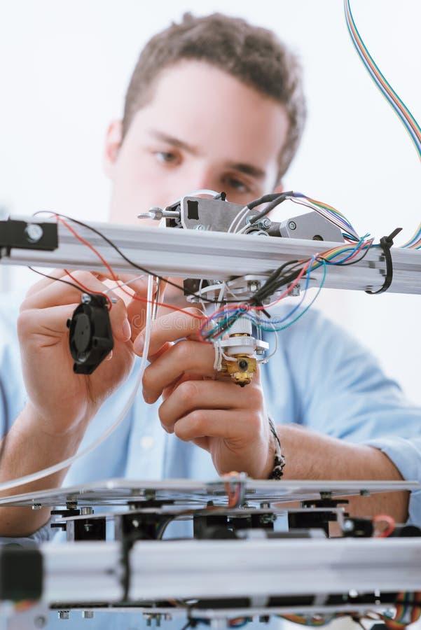 Junger Ingenieur, der einen Drucker 3D verwendet stockfoto