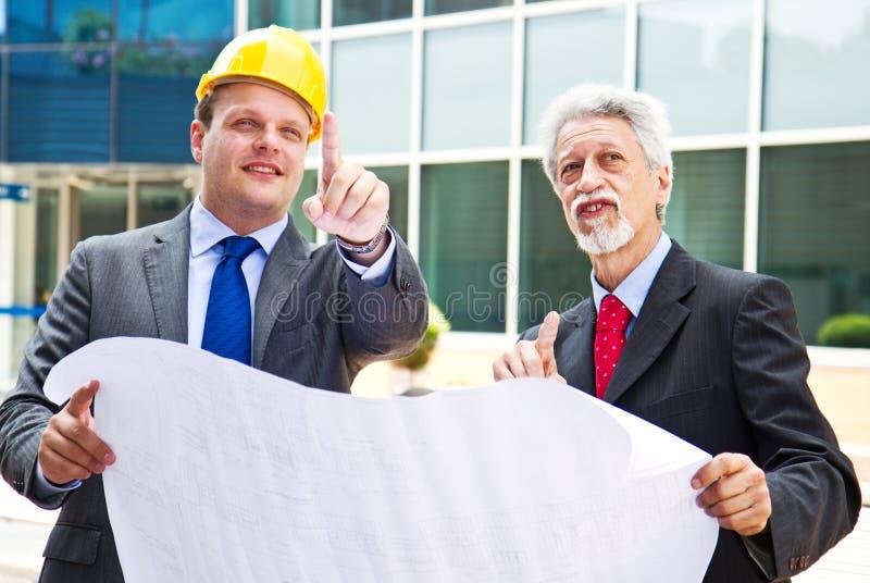 Junger Ingenieur, der seinem Partner etwas an der Baustelle zeigt lizenzfreies stockbild