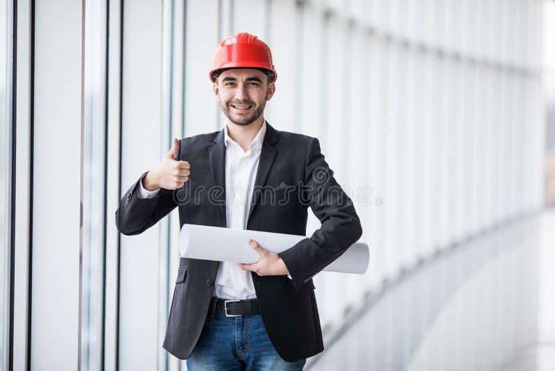Junger Ingenieur mit den Daumen oben zuhause nahe panoramischen Fenstern stockbilder