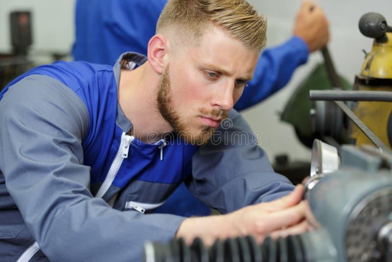 Junger Ingenieur unter Verwendung der Maschinerie in der Werkstatt lizenzfreies stockbild