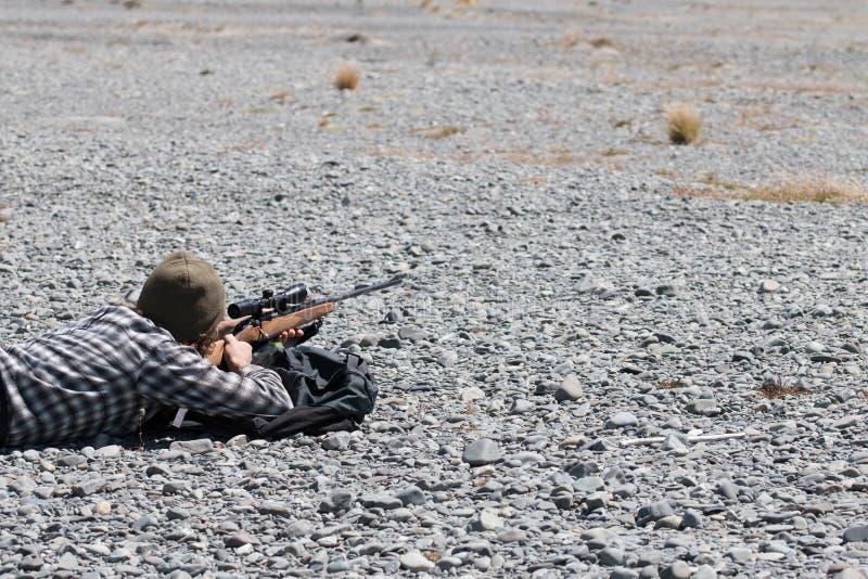 Junger Jäger, der aus den Grund liegt und den Anblick betrachtet lizenzfreie stockfotos