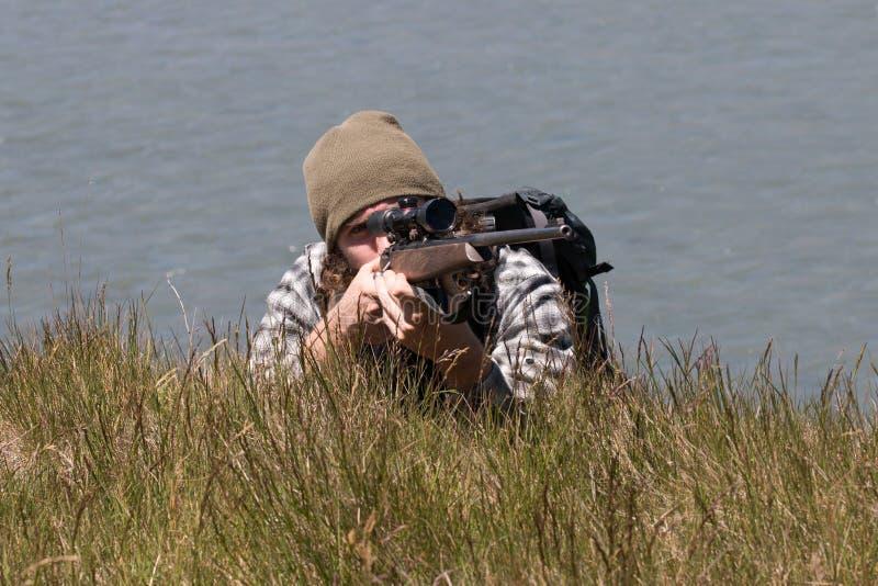 Junger Jäger mit Gewehr liegt auf Flussufer stockfotos