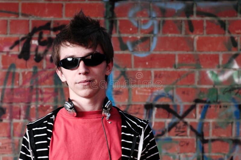 Junger Jugendlicher gegen Graffiti-Wand lizenzfreies stockfoto