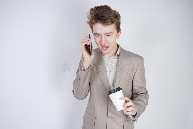 Junger Jugendlicher mit ?berraschten Gef?hlen in der grauen Gesch?ftskleidung, die mit Handy- und Papiertasse kaffee auf wei?em S lizenzfreies stockbild