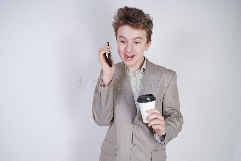 Junger Jugendlicher mit ?berraschten Gef?hlen in der grauen Gesch?ftskleidung, die mit Handy- und Papiertasse kaffee auf wei?em S lizenzfreies stockfoto