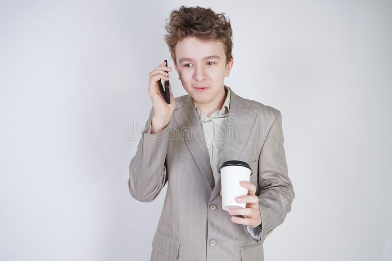 Junger Jugendlicher mit ?berraschten Gef?hlen in der grauen Gesch?ftskleidung, die mit Handy- und Papiertasse kaffee auf wei?em S stockfotografie