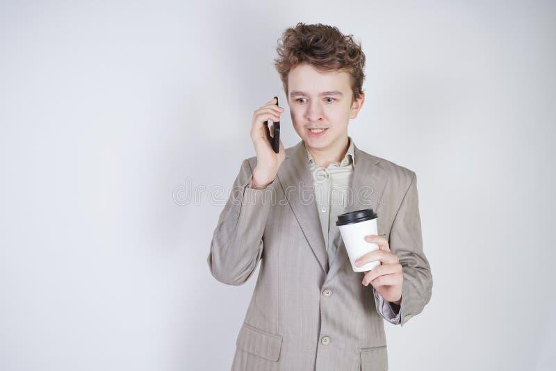 Junger Jugendlicher mit ?berraschten Gef?hlen in der grauen Gesch?ftskleidung, die mit Handy- und Papiertasse kaffee auf wei?em S stockfotos