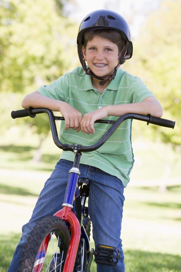Junger Junge auf Fahrrad draußen lächelnd stockbilder