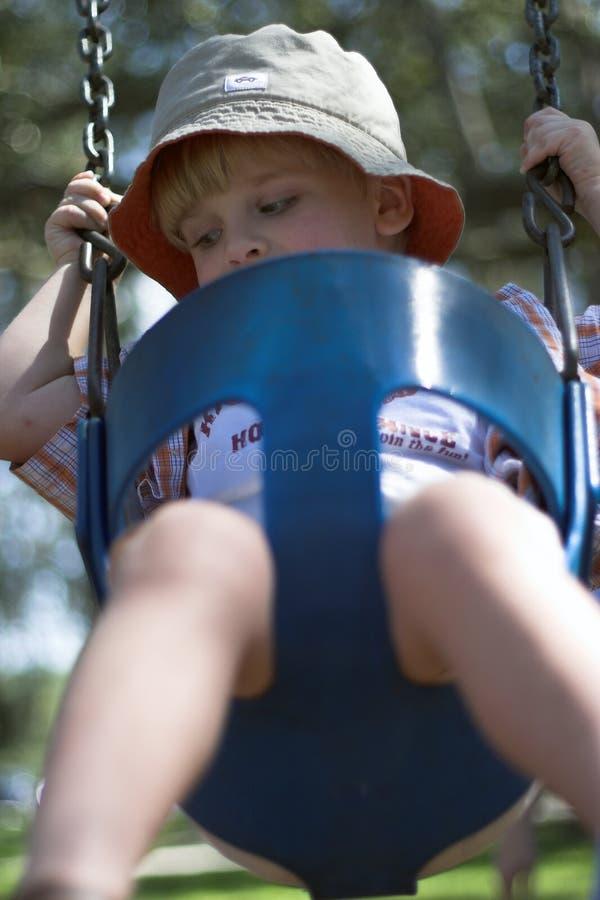 Junger Junge auf Schwingen am Spielplatz stockfotos