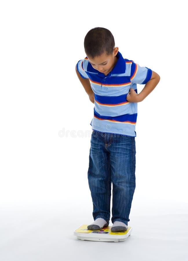 Junger Junge auf Skala stockbild