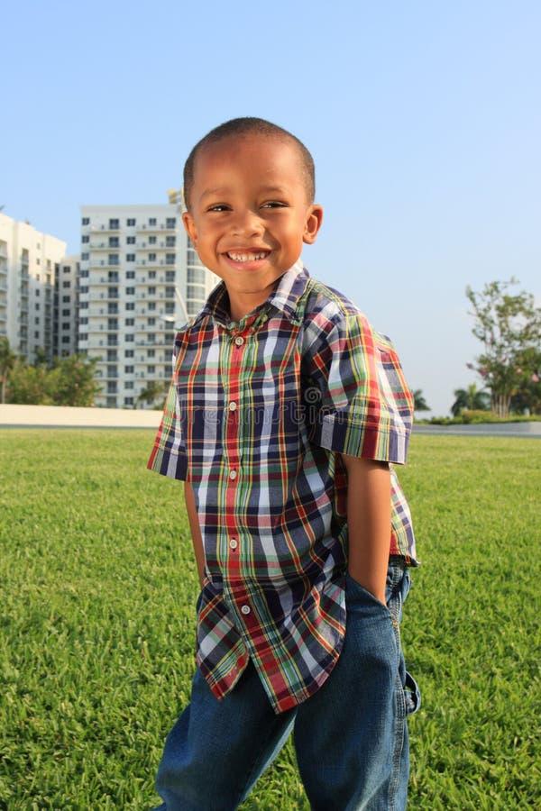 Junger Junge, der auf dem Gras aufwirft lizenzfreie stockbilder