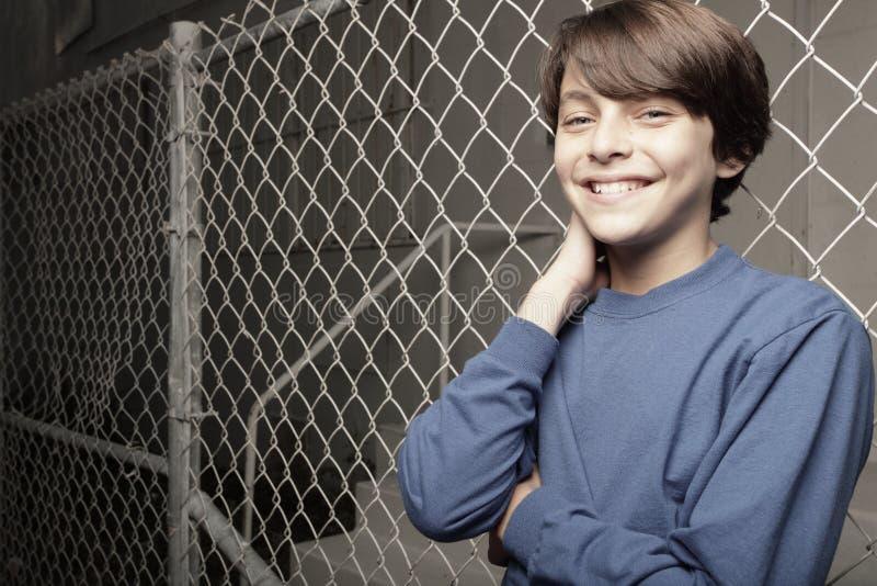 Junger Junge, der auf einem Kettelink Zaun aufwirft stockfoto