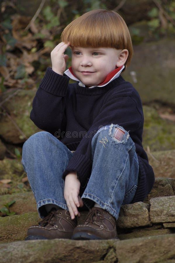 Junger Junge, der auf Treppen sitzt stockfoto