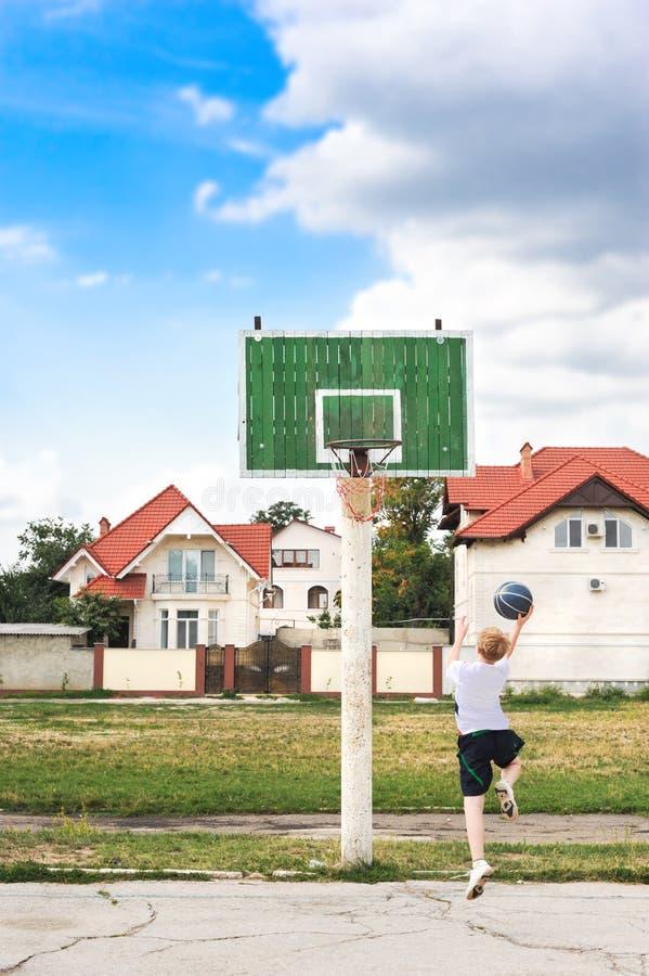Junger Junge, der Basketball alleine spielt lizenzfreies stockfoto