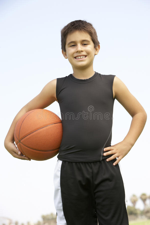 Junger Junge, der Basketball spielt stockbild