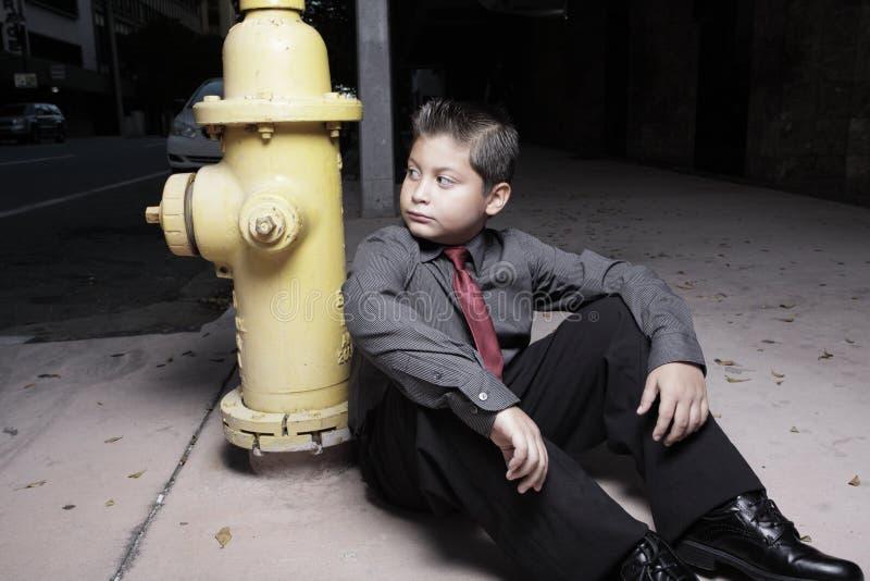 Junger Junge, der durch einen Feuerhydranten sitzt stockbild