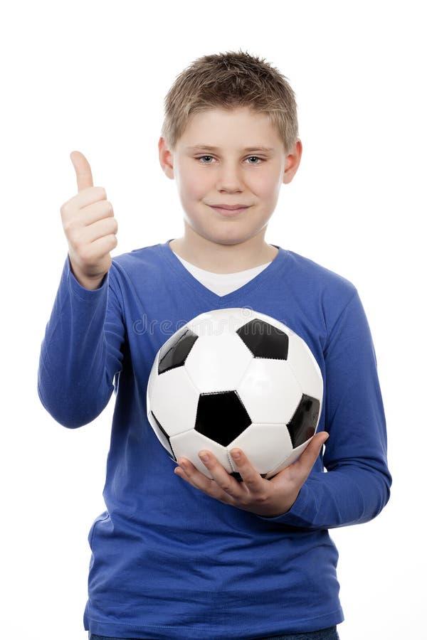 Junger Junge, der eine Fußballkugel anhält stockfoto