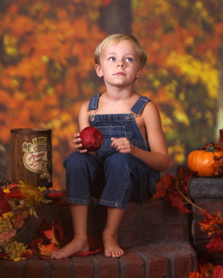Junger Junge, der einen Apfel anhält lizenzfreie stockfotografie