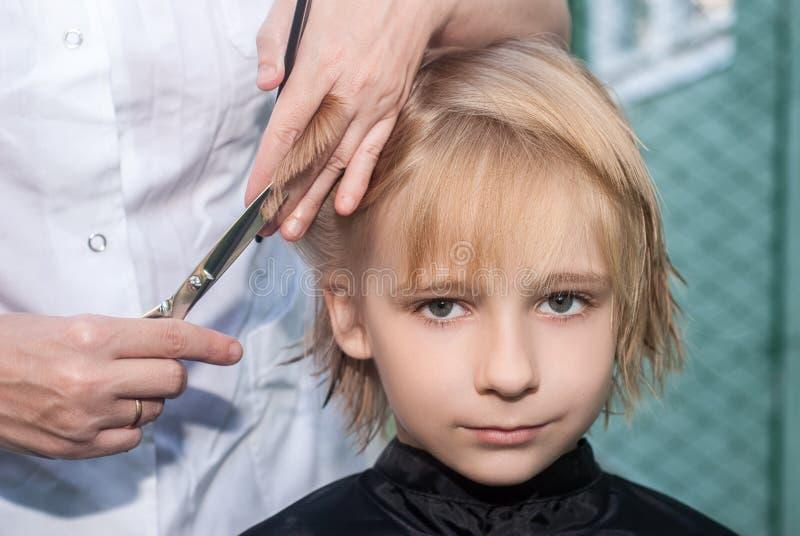 Junger Junge, der einen Haarschnitt erhält stockbild